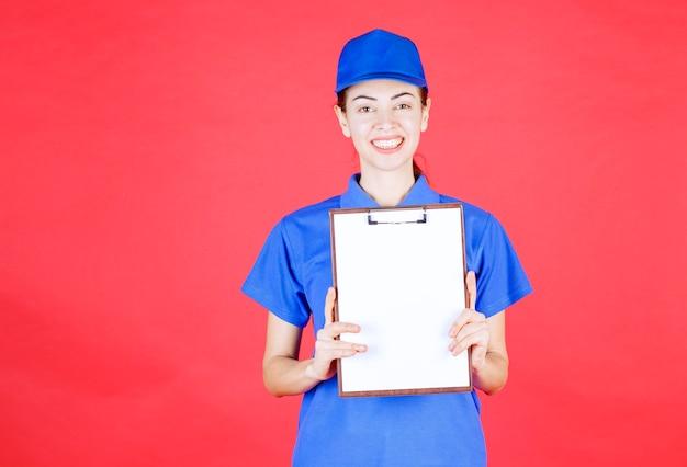 署名リストを提示する青い制服を着た女性の宅配便。