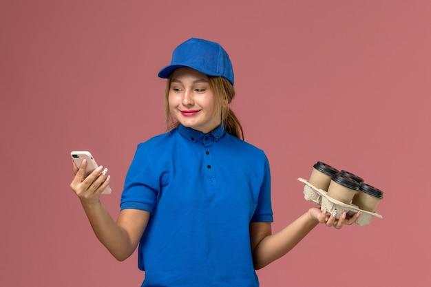 Женщина-курьер в синей форме использует свой телефон и держит коричневые чашки кофе на светло-розовом, доставка рабочей одежды