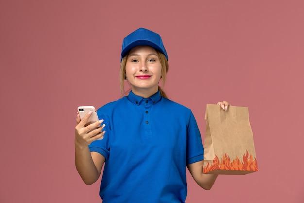 淡いピンク色の微笑みを浮かべて食品パッケージを保持している彼女の電話を使用して青い制服を着た女性の宅配便、サービス制服配達の仕事