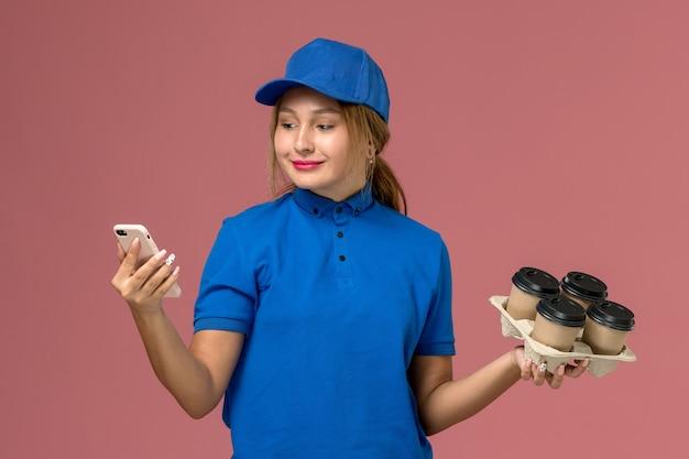 Женщина-курьер в синей форме разговаривает по телефону с коричневыми чашками кофе на светло-розовом, доставка рабочей формы