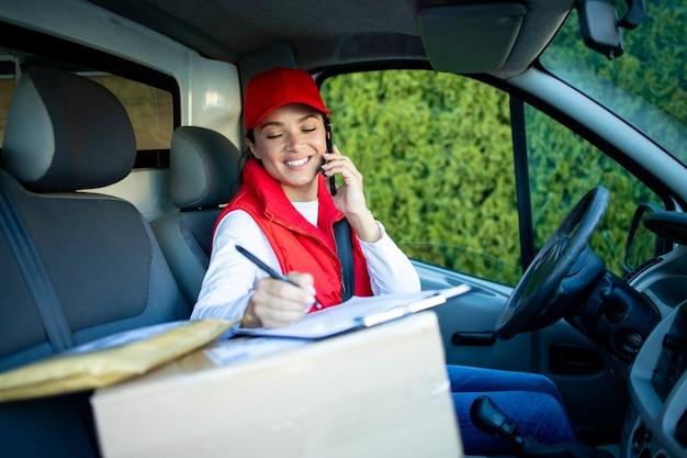 Женский курьер в фургоне доставки разговаривает по телефону.