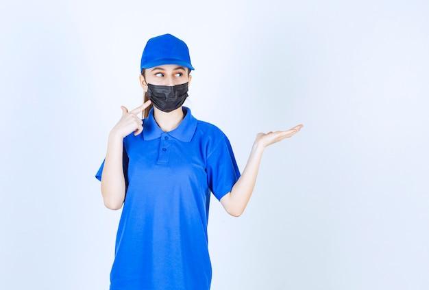 마스크와 파란색 유니폼을 입고 오른쪽에 뭔가를 보여주는 여성 택배.