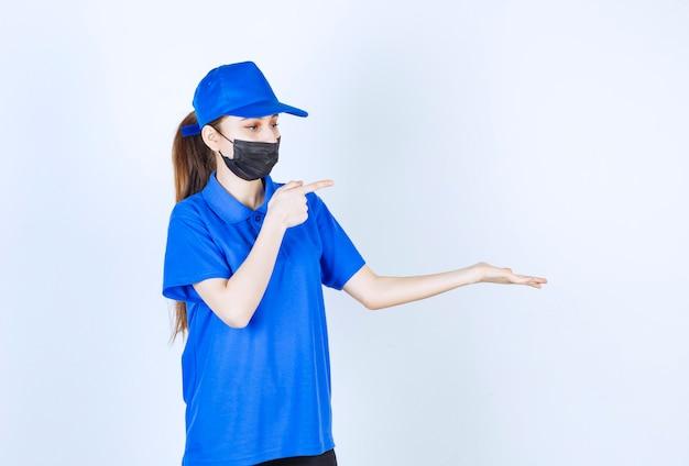 Женский курьер в маске и синей форме и показывает что-то справа