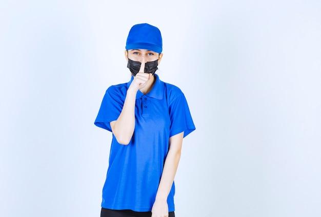 마스크와 파란색 유니폼의 여성 택배는 입을 닫고 침묵을 요구합니다.