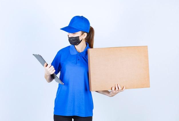 큰 판지 소포와 검은색 주소 폴더를 들고 마스크와 파란색 유니폼을 입은 여성 택배