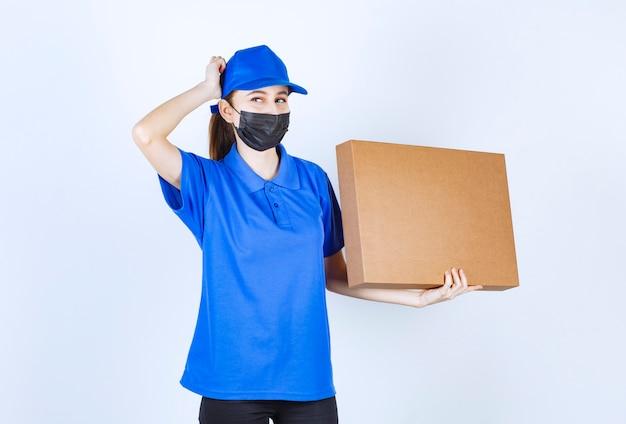 Курьер-женщина в маске и синей форме держит большой картонный пакет и выглядит смущенным и нерешительным.
