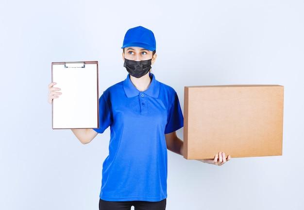 Женский курьер в маске и синей форме держит большой картонный пакет и представляет контрольный список для подписи.