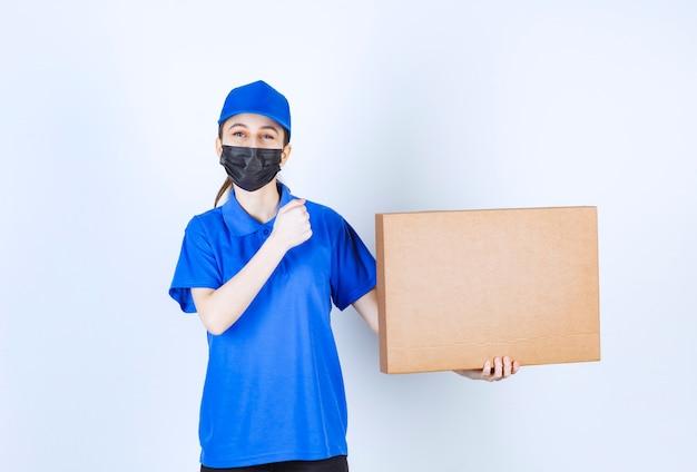 大きな段ボールの小包を保持し、彼女の拳を見せてマスクと青い制服を着た女性の宅配便