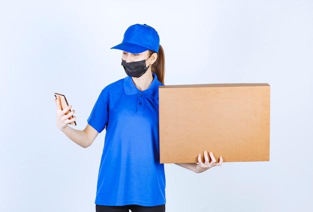 Курьер-женщина в маске и синей форме держит большую картонную посылку и принимает новые заказы по телефону