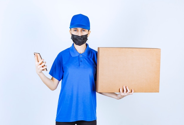 마스크와 파란색 유니폼을 입은 여성 택배사는 큰 판지 소포를 들고 전화로 새로운 주문을 받습니다.