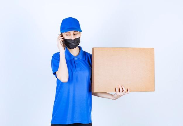 Женский курьер в маске и синей форме держит большую картонную посылку и разговаривает по телефону