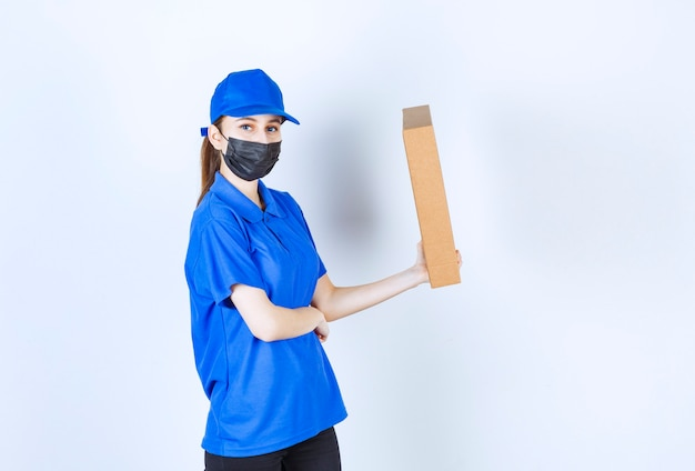 Женский курьер в маске и синей форме держит большой картонный пакет.