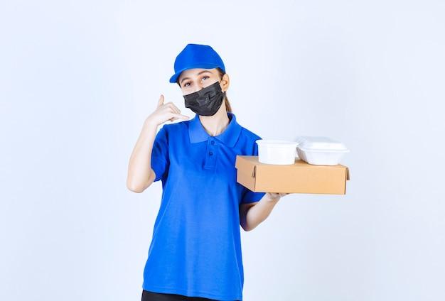 Женский курьер в маске и синей форме держит картонную коробку и пакеты на вынос и просит о звонке