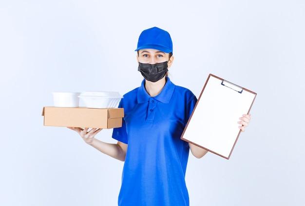 Женский курьер в маске и синей форме держит картонную коробку, пакеты на вынос и представляет контрольный список для подписи.