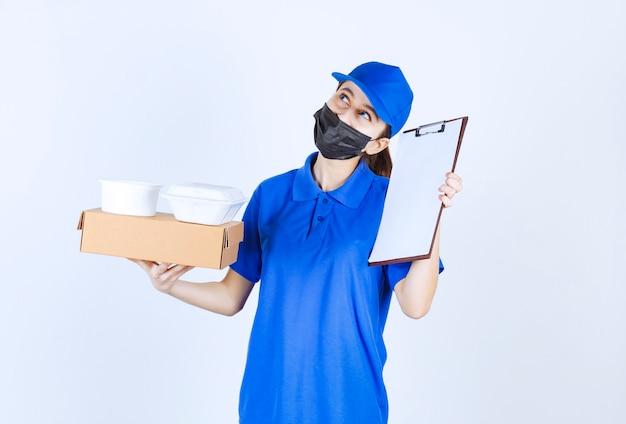 Женский курьер в маске и синей форме держит картонную коробку, пакеты на вынос и представляет контрольный список на подпись