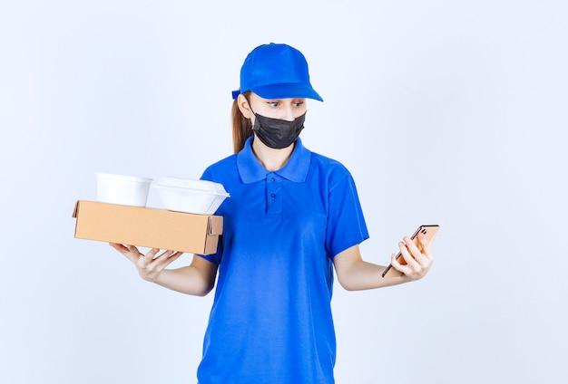 Женский курьер в маске и синей форме держит картонную коробку, пакеты на вынос и делает селфи