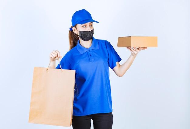 Женский курьер в маске и синей форме держит картонную хозяйственную сумку и коробку.