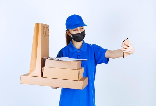 Женский курьер в маске и синей форме держит картонную хозяйственную сумку и несколько коробок, делая селфи.
