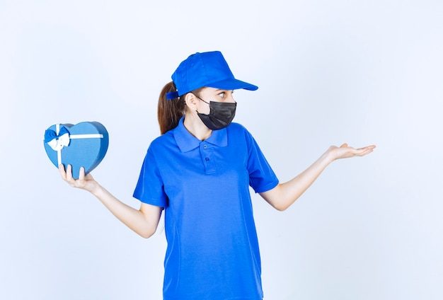 ハート型のギフトボックスを持って誰かにそれを受け取るように呼びかけるマスクと青い制服を着た女性の宅配便。