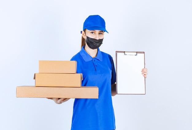 段ボール箱の在庫を保持し、署名リストを提示するマスクと青い制服を着た女性の宅配便