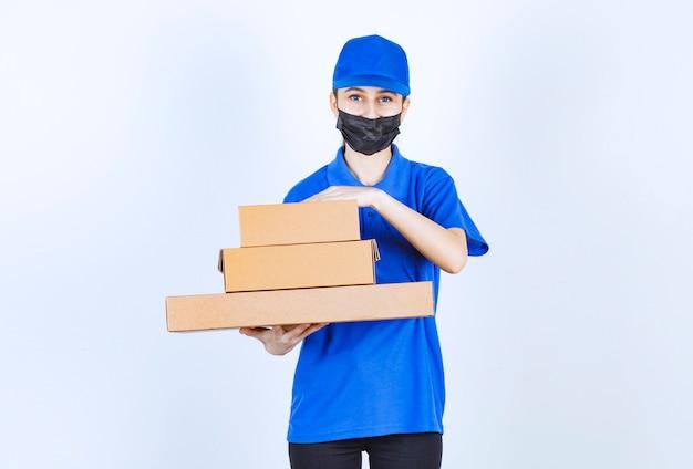 Женский курьер в маске и синей форме держит картонную коробку