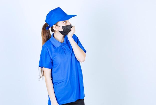 마스크와 파란색 유니폼을 입은 여성 택배는 겁에 질려 겁에 질려 보인다