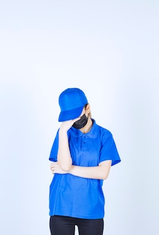 마스크와 파란색 유니폼을 입은 여성 택배는 졸리고 피곤해 보입니다.