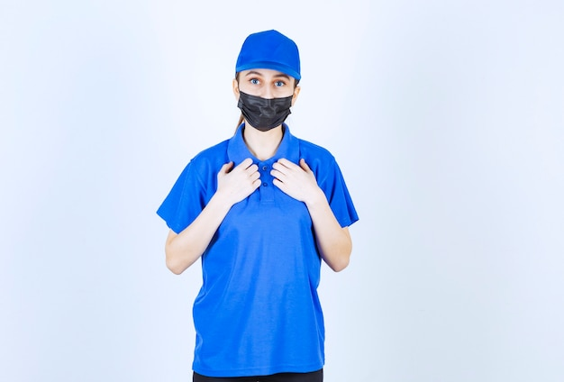 마스크와 자신을 가리키는 파란색 유니폼 여성 택배.