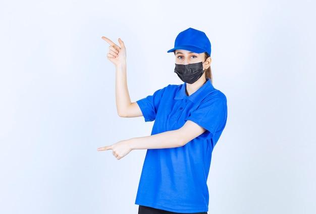 마스크를 쓰고 왼쪽을 가리키는 파란색 유니폼을 입은 여성 택배.