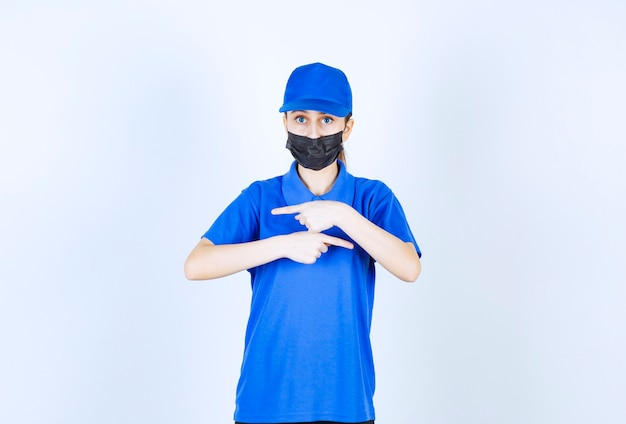 마스크와 파란색 유니폼을 입은 여성 택배기사가 양면을 보여줍니다.