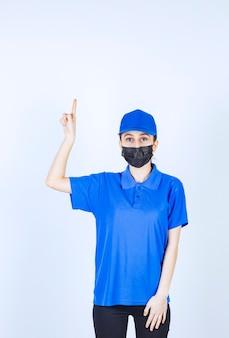 마스크와 파란색 유니폼을 입은 여성 택배기사가 아래에 무언가를 보여줍니다.