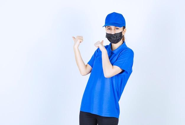 마스크와 뒤에 뭔가 보여주는 파란색 유니폼 여성 택배.