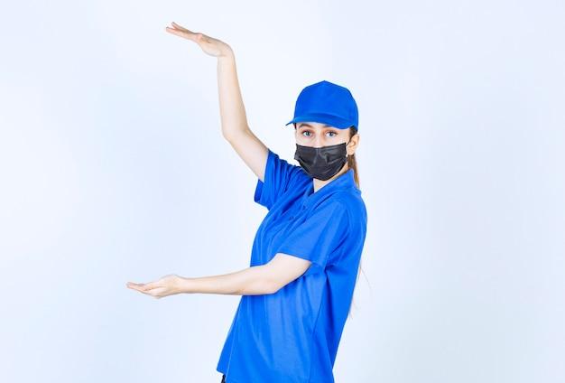 물체의 높이를 보여주는 마스크와 파란색 유니폼을 입은 여성 택배