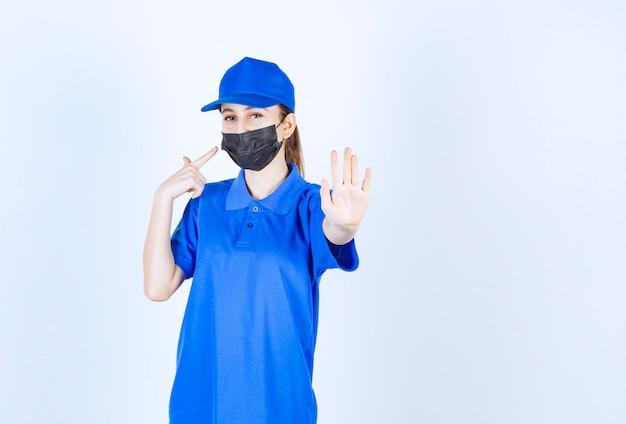 마스크와 파란색 제복을 입은 여성 택배.