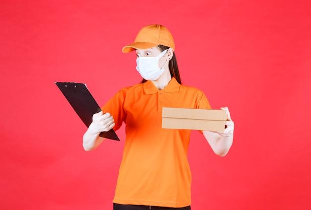 Курьер-женщина в оранжевом дресс-коде и маске держит картонную коробку и читает имя и адрес