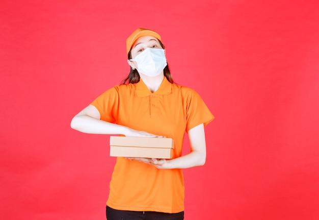 Женский курьер в дресс-коде оранжевого цвета и маске, держащей картонную коробку.