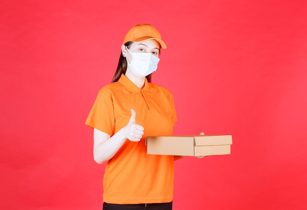 オレンジ色のユニフォームと段ボール箱を保持し、肯定的な手のサインを示すマスクの女性の宅配便。