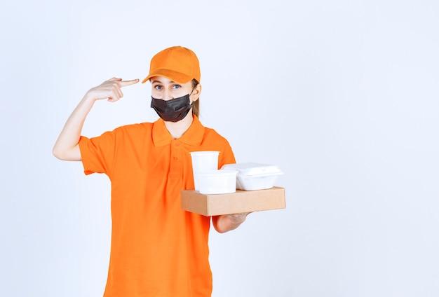 Курьер-женщина в оранжевой форме и черной маске держит картонную посылку, берет еду и напитки на вынос, размышляя и планируя