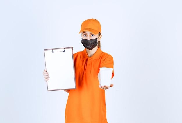 Курьер-женщина в оранжевой форме и черной маске держит пластиковый стаканчик на вынос и представляет бланк для подписи для передачи