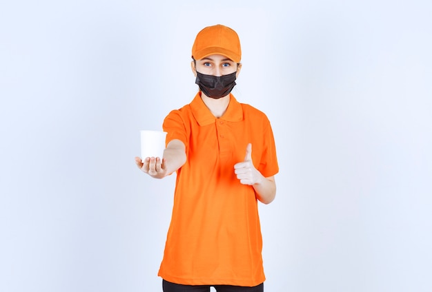 Женский курьер в оранжевой форме и черной маске держит напиток на вынос и наслаждается вкусом