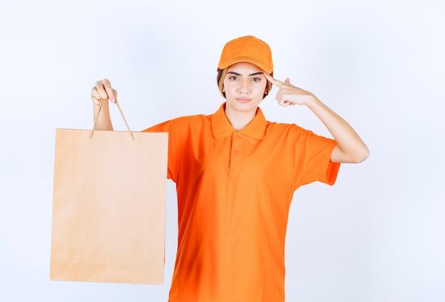 마분지 쇼핑백을 배달하고 사려깊게 보이는 주황색 제복을 입은 여성 택배