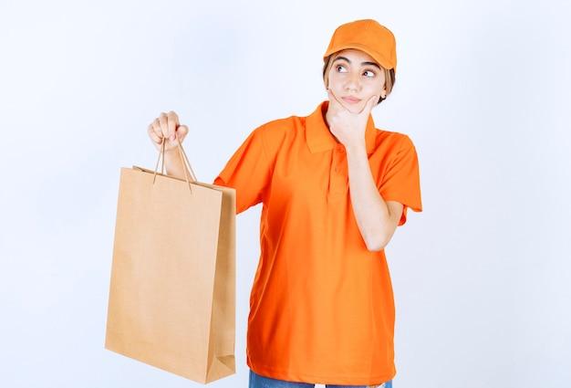 段ボールの買い物袋を提供し、思慮深く見えるオレンジ色の制服を着た女性の宅配便