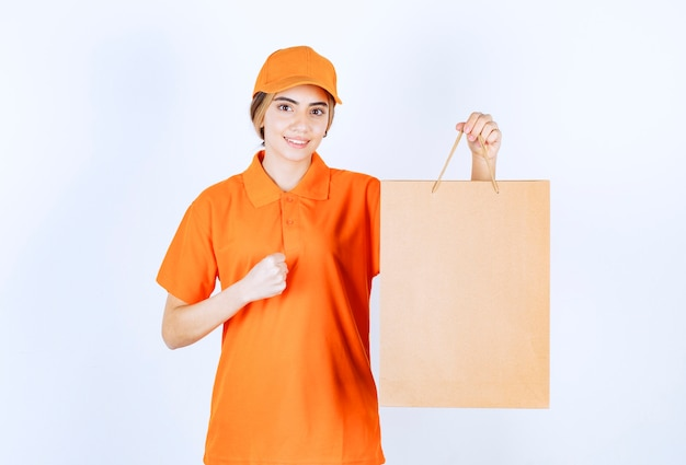 주황색 제복을 입은 여성 택배기사가 판지 쇼핑백을 배달하고 즐거움 표시를 보여줍니다.
