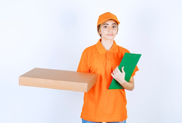 Женский курьер в оранжевой форме держит картонную коробку и зеленый список клиентов