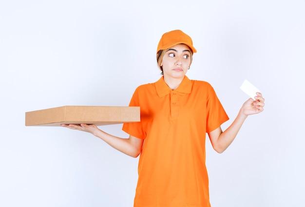 Женский курьер в оранжевой форме держит картонную коробку и представляет свою визитную карточку