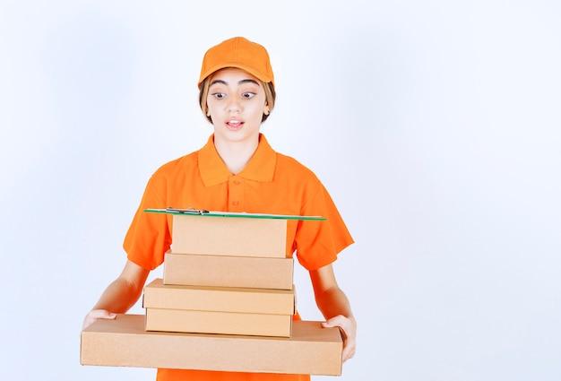 마분지 소포를 들고 오렌지색 유니폼을 입은 여성 택배사는 혼란스럽고 사려깊게 보입니다.
