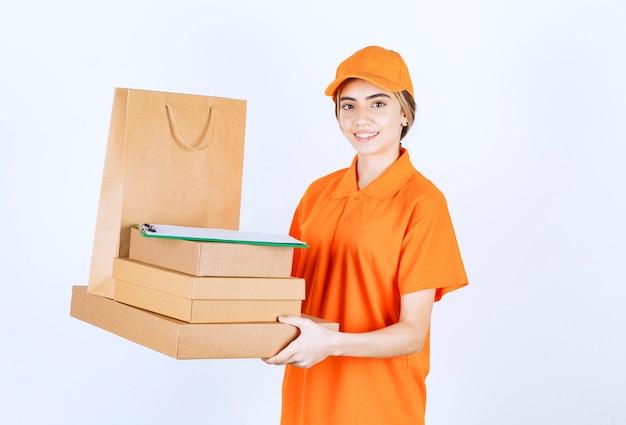 마분지 소포와 쇼핑백을 들고 있는 주황색 제복을 입은 여성 택배