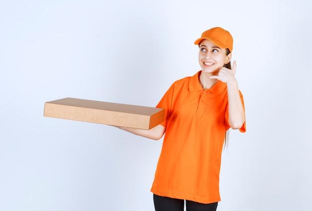 Женский курьер в оранжевой форме держит коробку для пиццы на вынос и просит позвонить