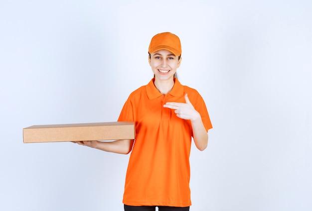Женский курьер в оранжевой форме держит коробку для пиццы на вынос