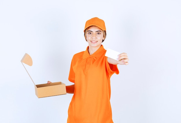 열린 판지 상자를 들고 고객에게 명함을 미리 설정하는 주황색 제복을 입은 여성 택배